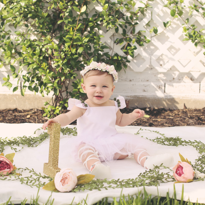 Lilyana's first birthday photoshoot and cake smash, featuring tutu romper with pompom trim from cuteheads
