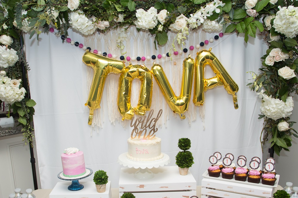 Tova's first birthday party floral backdrop with navy and pink garland