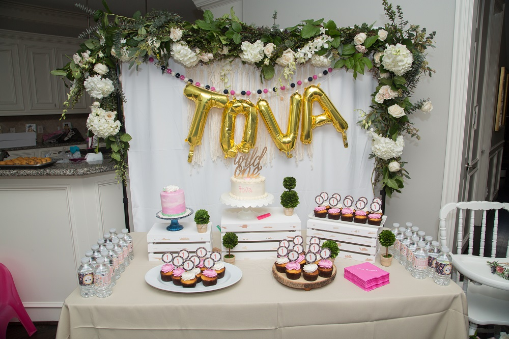 Tova's first birthday party floral backdrop and dessert table