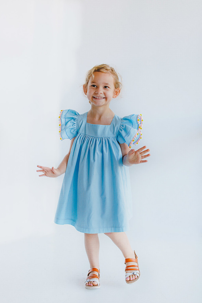 cuteheads Bella dress | blue cotton dress with pom pom trim flutter sleeves