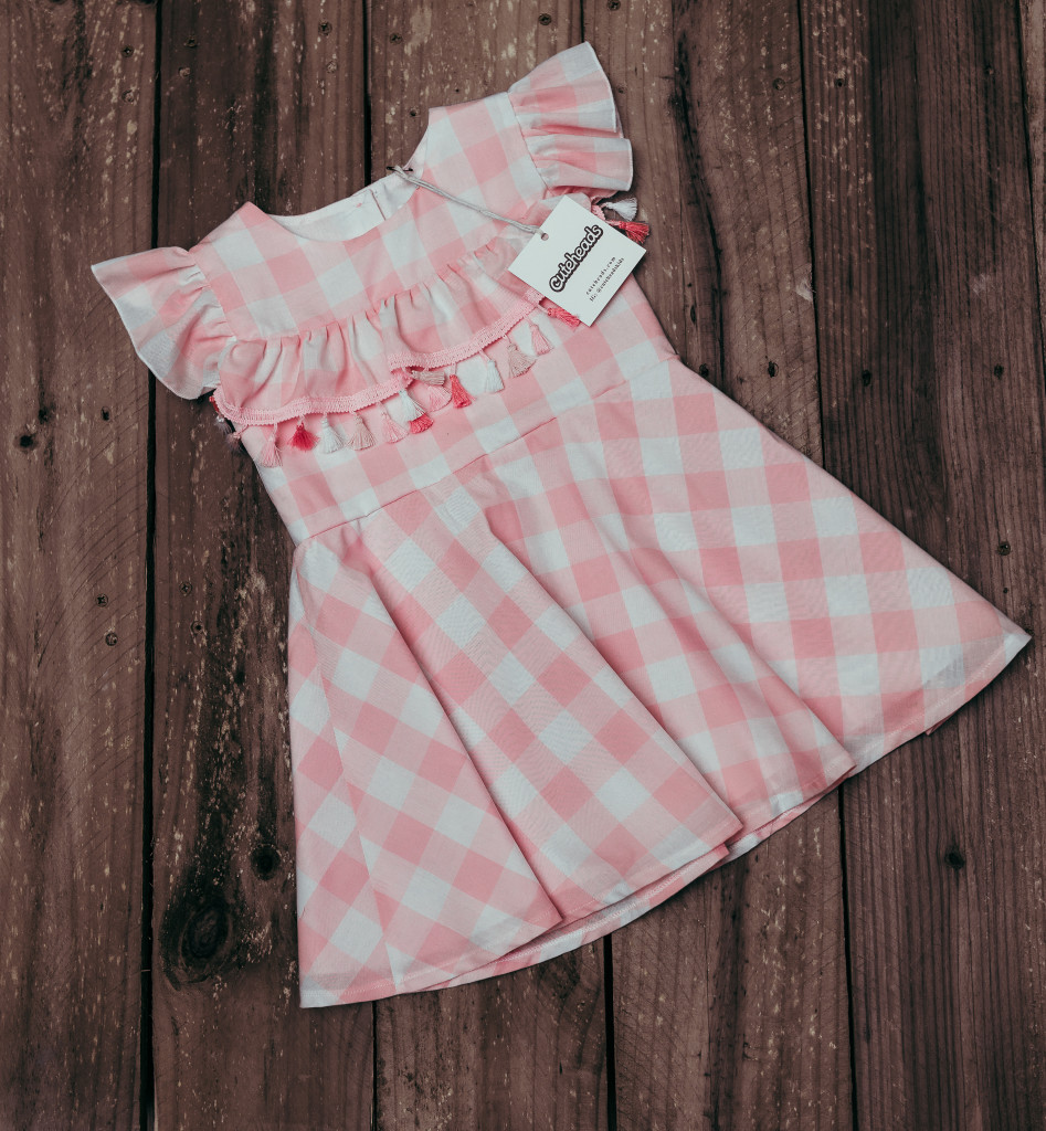 Introducing a subscription box for girls that your daughter will love. Get a surprise dress in the mail every month! Learn more at cuteheads.com. // The cuteheads pink buffalo plaid tassel dress, only available in the Mystery Box!